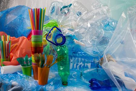 Borse e lettiere. Forchette di plastica colorate poste in un bicchiere di plastica e in piedi vicino a un mucchio di spazzatura come risultato della cattura della plastica