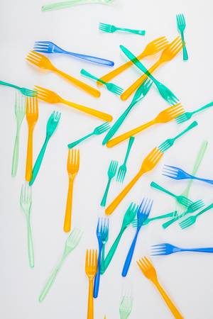 Causing global warming. Bright and colorful dangerous plastic forks affecting nature and being result of greenhouse gases Banque d'images
