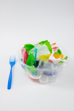 Dangerous plastic. Clear transparent container filled with trash and garbage with prepared fork nearby Banque d'images