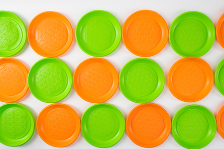 Mindful consumption. Colorful bright green and orange disposable plates lying in rows as art installation