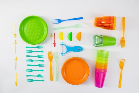 Mindful using. Bright plates and forks lying with skewers and cups made of cheap dangerous plastic Banque d'images