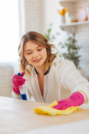 No dust. Pleasant young woman smiling while cleaning a counter surface with a special cleansing agent