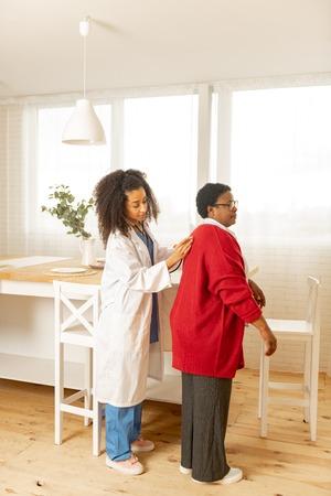 Examining woman. Private professional nurse wearing uniform using stethophone while examining woman