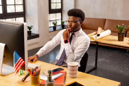 Análisis de negocio. Hombre serio pensativo comprobando la información mientras mira la pantalla del portátil