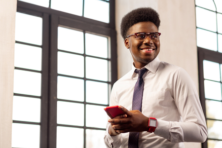 Successful worker. Positive confident man smiling while standing with his mobile phone in the office