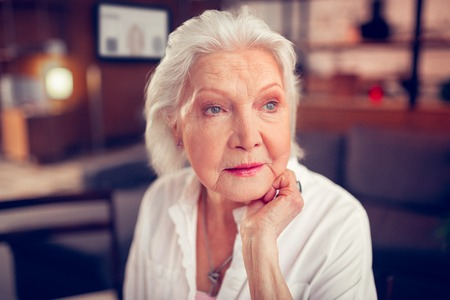 Blue-eyed aged lady. Close up of beautiful blue-eyed aged lady feeling really excited and happy