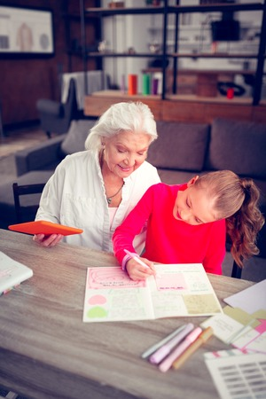 Cute granddaughter. Cute dark-haired granddaughter sending time with her loving granny while coloring pictures