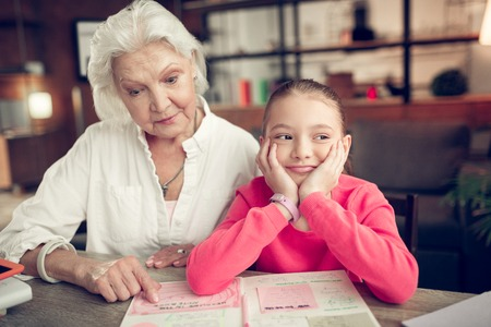 Homework with granny. Cheerful cute dark-haired girl feeling funny while doing homework with loving granny Banque d'images