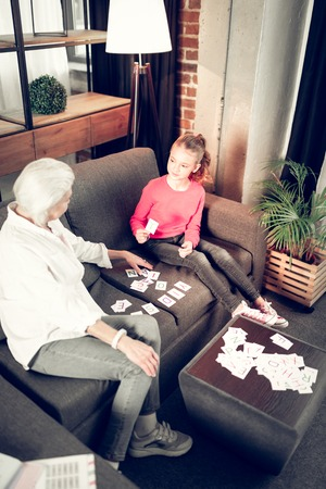 Grandmother teaching. Grey-haired grandmother teaching her cute and smart girl at the weekend