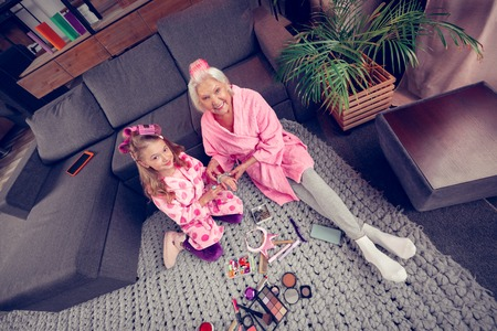 Before doing makeup. Cute girl and granny wearing hair rollers sitting on floor before doing makeup