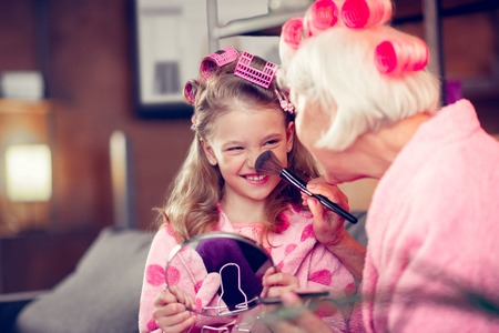 Brush on nose. Cute little girl smiling while doing makeup with granny having cosmetics brush on her nose