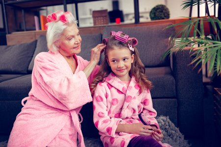 Putting hair curlers. Caring grey-haired granny putting hair curlers on hair of her cute little girl