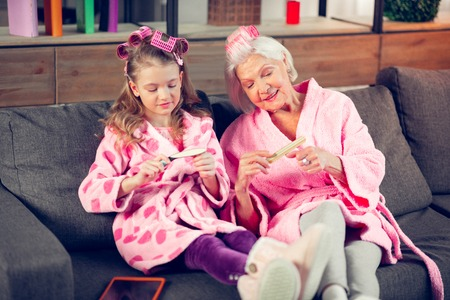 Using nail files. Grandmother and granddaughter in pink bathrobes using nail files while having beauty day