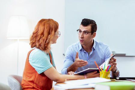 Young teacher. Nice handsome man talking to his student while explaining her the material