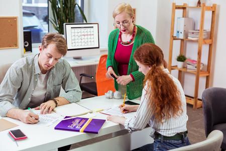 Profesjonalna nauczycielka. Miła, doświadczona nauczycielka stojąca blisko swoich uczniów, pomagająca im w nauce