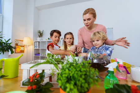 Table with plants. Three pupils and their teacher standing near table with plants at the ecology lesson Stock Photo