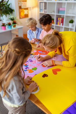 Teacher helping pupils. Blonde-haired young teacher helping pupils painting and making cutouts