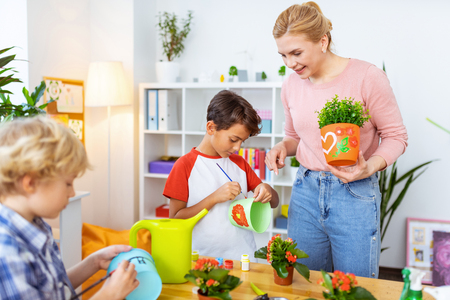 Painting time. Blonde-haired beaming ecology teacher watching her cute pupils coloring flowerpots Stock Photo