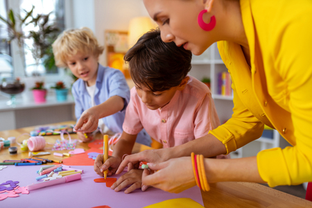 Shape of heart. Young teacher wearing pink earrings helping boy to make cutout in the shape of heart