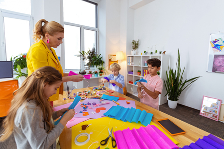 Assisting pupils. Blonde-haired teacher wearing yellow jacket assisting her pupils making applied ornament