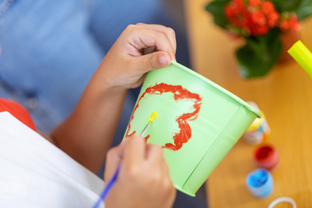 Painting cute flower. Close up of schoolboy painting cute flower on flowerpot at ecology lesson Stock Photo