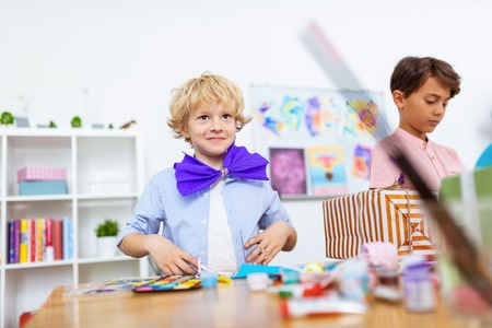 Boy smiling. Blonde-haired handsome and cute boy smiling while wearing paper bow at the art lesson