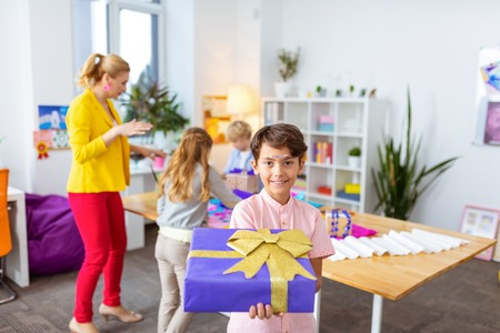 Showing present box. Handsome dark-haired boy showing nice present box after decorating it in class