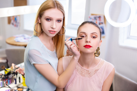 Evening makeup. Face of an attractive beautiful young woman while having her makeup applied Stock fotó
