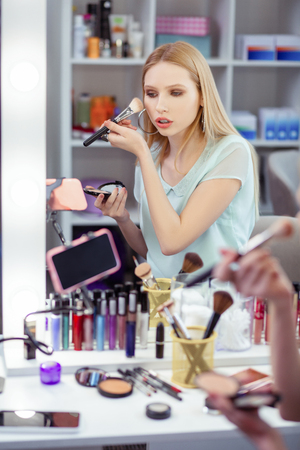 Successful blogger. Nice young woman recording a video on her smartphone while having her beauty blog