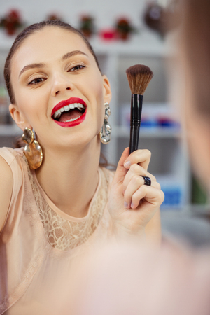 Perfect beauty. Joyful nice woman smiling to her reflection while holding a makeup brush