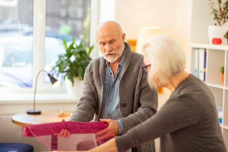Teamwork and cooperation. Pleasant aged people working together in team while packing gifts Stock Photo