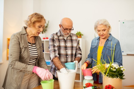 Engaged in gardening. Serious aged people looking into the flower pots while being engaged in gardening