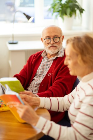 Eyesight problems. Serious good looking aged man wearing glasses while sitting with a book