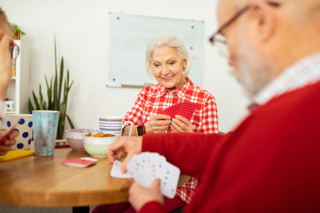 Engaging entertainment. Pleasant senior woman holding her cards while playing with her friend Banco de Imagens
