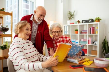 Look here. Joyful senior women smiling while showing books to their friend Zdjęcie Seryjne