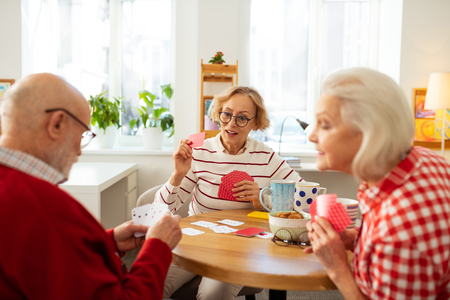 Favourite entertainment. Good looking aged people sitting around the round table while playing card games Stock Photo