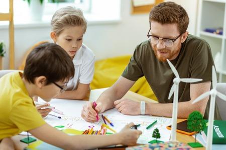 Ausgestattetes helles Klassenzimmer. Ingwer gutaussehende Lehrerin mit rotem Bart, die mit bunten Bleistiften und Markern auf das Papier schreibt Standard-Bild