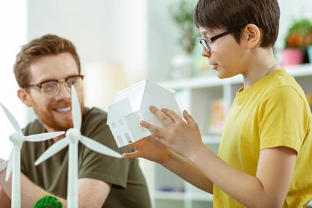 Lecciones cognitivas. Niño curioso de pelo oscuro sosteniendo una casa de plástico blanco mientras observa un ejemplo de infraestructura de molino de viento Foto de archivo