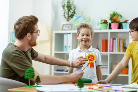 Equipped classroom. Bearded ginger teacher rewarding his little student for love to nature with special signs Standard-Bild