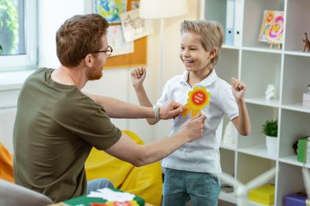 Lehrer, der Zeichen anwendet. Strahlendes aktives Kind im weißen T-Shirt mit einem hellen, lohnenden Zeichen für großartige Arbeit während des Kurses Standard-Bild