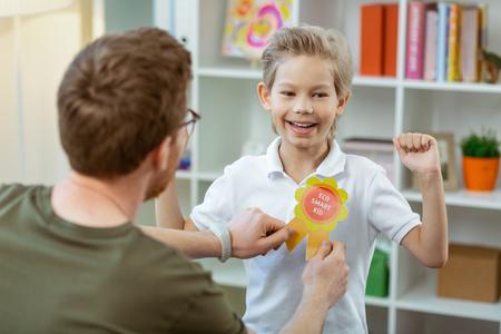 Helles lohnendes Zeichen. Zufriedener stolzer Junge, der sich über seine Belohnung von einem netten Grundschullehrer freut Standard-Bild