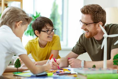 Cognitief project. Lachende kortharige man met een heldere bril die kleine jongens helpt met een projectieve poster voor zijn lessen Stockfoto