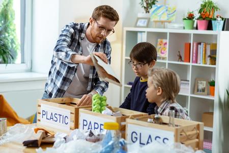 Toller Lehrer. Aufmerksamer Lehrer im karierten Hemd, der seinen Schülern die Grundlagen der Mülltrennung beschreibt Standard-Bild
