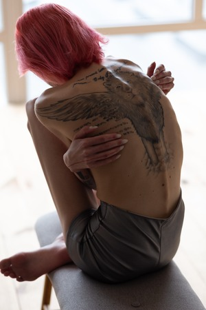 Tattoo on back. Skinny red-haired woman with big tattoo on her back suffering from anorexia