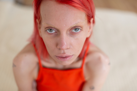 Grey-eyed woman. Skinny grey-eyed woman with red hair suffering from anorexia and stomachache