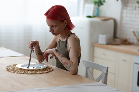 Suffering from anorexia. Red-haired woman with eating disorder eating nothing suffering from anorexia