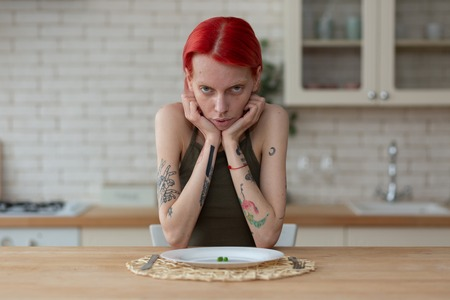 Woman with anorexia. Skinny woman suffering from anorexia sitting in the kitchen near plate with peas