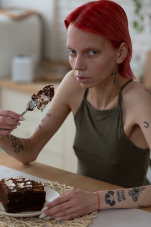 Eating chocolate cake. Skinny woman with tattoos suffering from anorexia eating chocolate cake