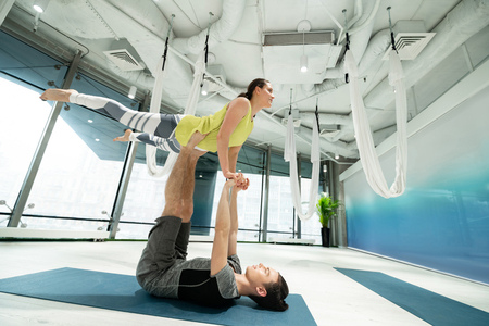 Couple doing yoga. Young sport couple feeling amazing while doing yoga together at the weekend