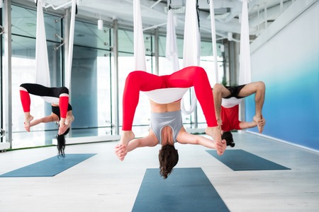 Bodies stretch. Active and fit women and man stretching their bodies while doing aerial yoga 写真素材